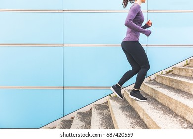 Woman jogging and running up a staircase. Girl wearing hi-tech clothes doing fitness activities outdoors. Healthy lifestyle and sport concepts