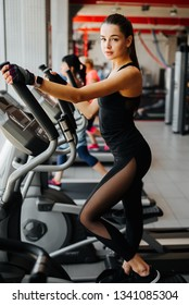 Woman in jogging sneakers running on elliptical machine at gym