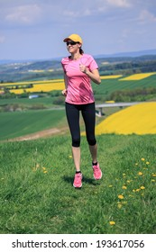 woman jogging through the fields at the springtime