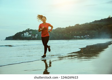 Woman jogging workout on the beach in the morning. Relax with the sea walk.