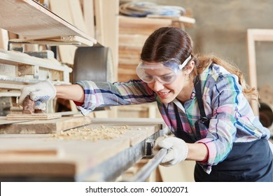 Woman as joiner grinding wood