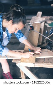 woman joiner in home workshop draws on a wooden Board pencil line saw cut