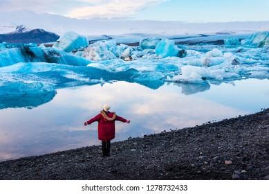 Woman at Jokulsarlon Glacier Lagoon in Iceland at sunset
