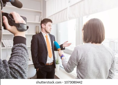 A woman journalist interviews a business man in a suit near a window in a room with a modern interior
