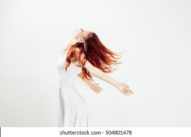 Woman joyful and happy in white dress. Flying hair. The concept of happiness