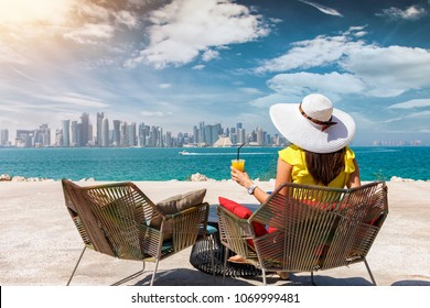 Woman with a juice in her hand enjoys the view to the skyline of Doha, Qatar, on a sunny day