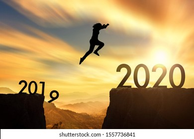 The woman jumping from 2019 cliff to 2020 cliff on sunrise time