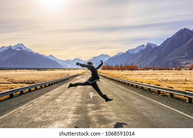 A woman jumping across an empty road in Aoraki Mount Cook National Park, South Island, New Zealand.