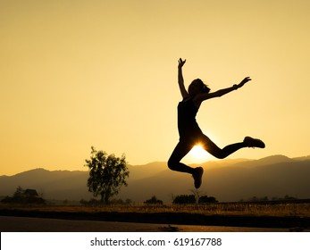 Woman jumping against beautiful sunset. Freedom, enjoyment concept.
