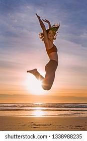 woman jumping at the beach at sunset