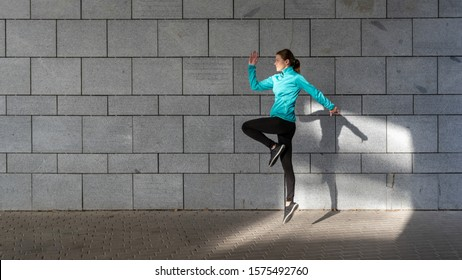 Woman jumping up in cardio workout, against wall with copy space on background. Side view of young adult sporty girl in sportswear and sneakers shoes spending time on sport training outdoor in city