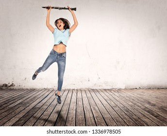 woman jumping with clarinet in her hands indoors