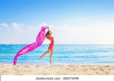 Woman jumping with cloth on a beach