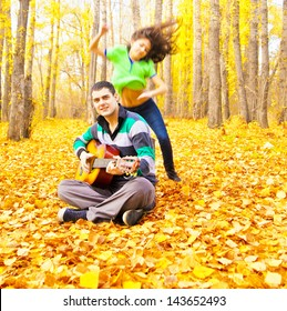 Woman jumping and dancing man sitting on a autumn forest with acoustic guitar Copy Space for inscription