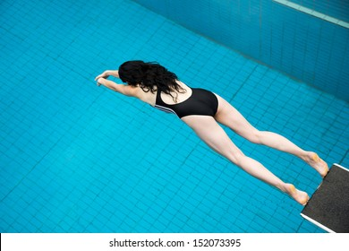 Woman jumping from a diving board at public swimming pool
