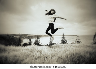 Woman jumping in front of a beautiful beach in Australia. Black and white vintage effect.