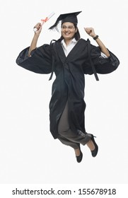 Woman jumping with her diploma in graduation gown