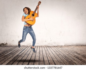 woman jumping indoors with classic guitar in her hands