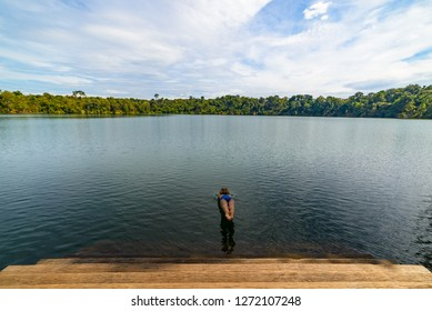 Woman jumping into the water of volcanic lake surrounded by forest in Banlung, Cambodia, travel destination