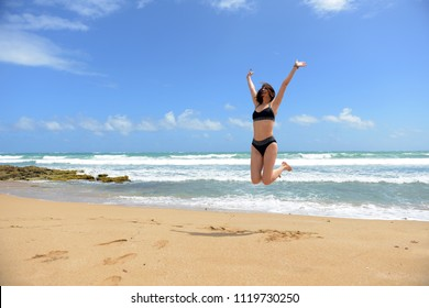 Woman jumping of joy in the beach with blue skies and sunny day