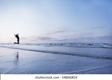 Woman jumping for joy on beach at sunrise