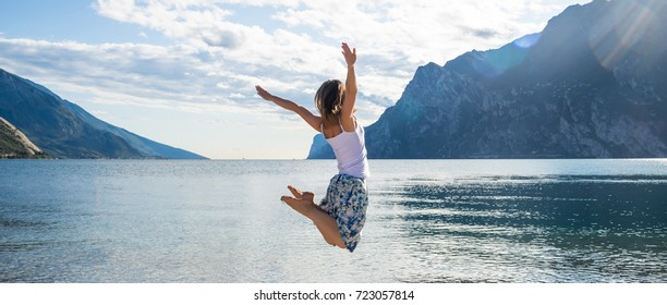 Woman jumping at the lake Garda. Italy