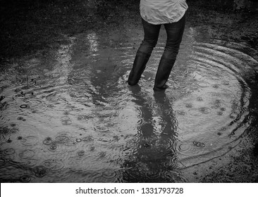 A woman jumping in a large puddle of water during the rain.