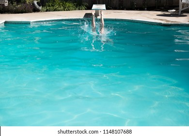Woman jumping off a diving board into a swimming pool, legs above the water. Woman diving into an outdoor swimming pool in the summer.