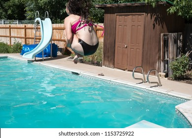 Woman jumping off diving board doing a cannon ball into a private swimming pool. Young woman mid air doing a cannon ball into an outdoor swimming pool in the summer. Summer fun in the pool.