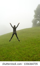 Woman jumping on a green hill foggy day