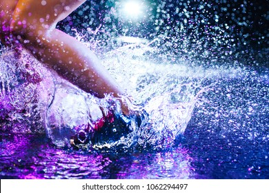 Woman jumping on water with big splashes. Legs and shoes close-up. Studio with rain and drops interior.