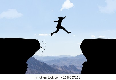Woman jumping over abyss.