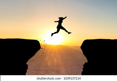 Woman jumping over abyss in front of sunset.