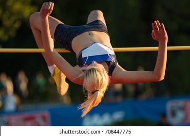 Woman jumping over bar at athletics meeting - high jump discipline.
