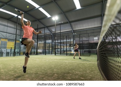 woman jumping for paddle tennis attack