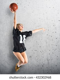 Woman jumping and playing basketball over grey background
