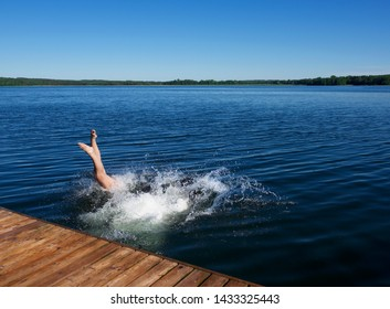 Woman jumping to the water. Lithuanian nature. Lake in lithuania and girl jumping to the water