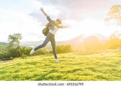 A woman jumps happily on the mountain at sunset.