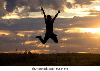 A woman jumps into the air with the setting sun in the background.
