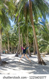 Woman jumps on the tropical island with palm tree on the beach. Concept happiness, woman jump on the beach. Asian travel to the Philippine islands