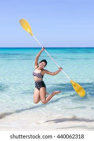 Woman jumps with a paddle on a sea beach