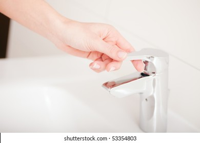 Woman (just hand to be seen) opening the water tap to wash her hands