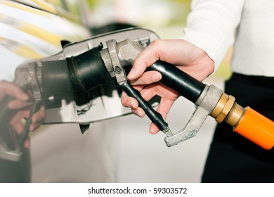 Woman - just hand to be seen - refueling her car with LPG gas at a station