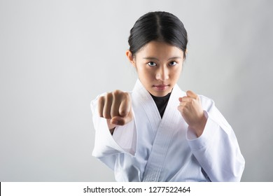 Woman in Karate suit performing a Karate punch on white background