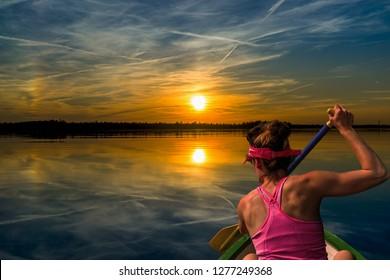 Woman kayaking on a lake at beautiful sunset