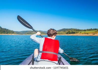 Woman kayaking on lake Lokve, young active girl on the Lokvarsko lake in Gorski kotar, Croatia, enjoying adventurous experience on a sunny day.