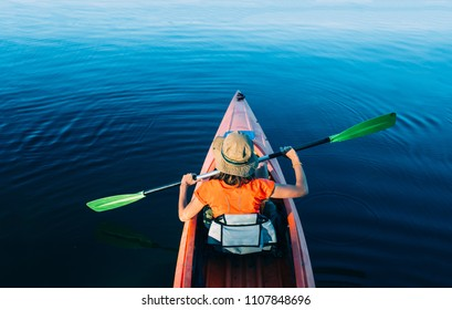 Woman kayaking, swinging paddle in air at lake, rear view, high angle view