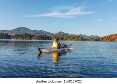 Woman kayaks within a white kayak in a remote lake called Boareas Ponds in the Adirondacks with the mountains in view