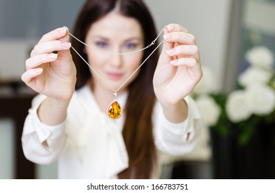 Woman keeping necklace with yellow sapphire at jeweler's shop. Concept of wealth and luxurious life