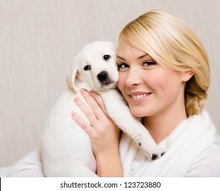 Woman keeping white labrador puppy near her face